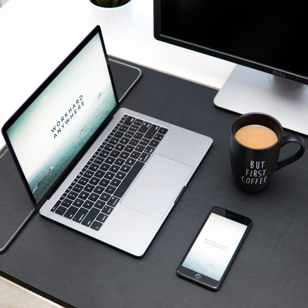 laptop, coffee mug, and iPhone on desk